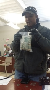 GPD SIU Agent Chardannay Hurst bags money into evidence that was seized in an operation that targeted what investigators say is a Crips hangout and location of drug sales that funds gang activities.